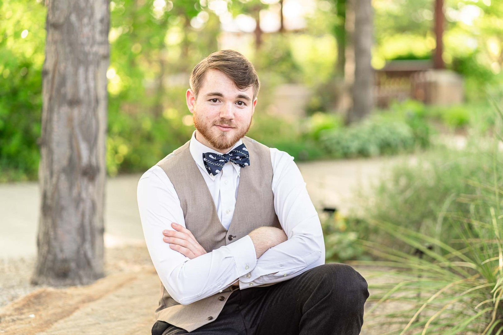 boy in vest and bow tie kneeling in a park