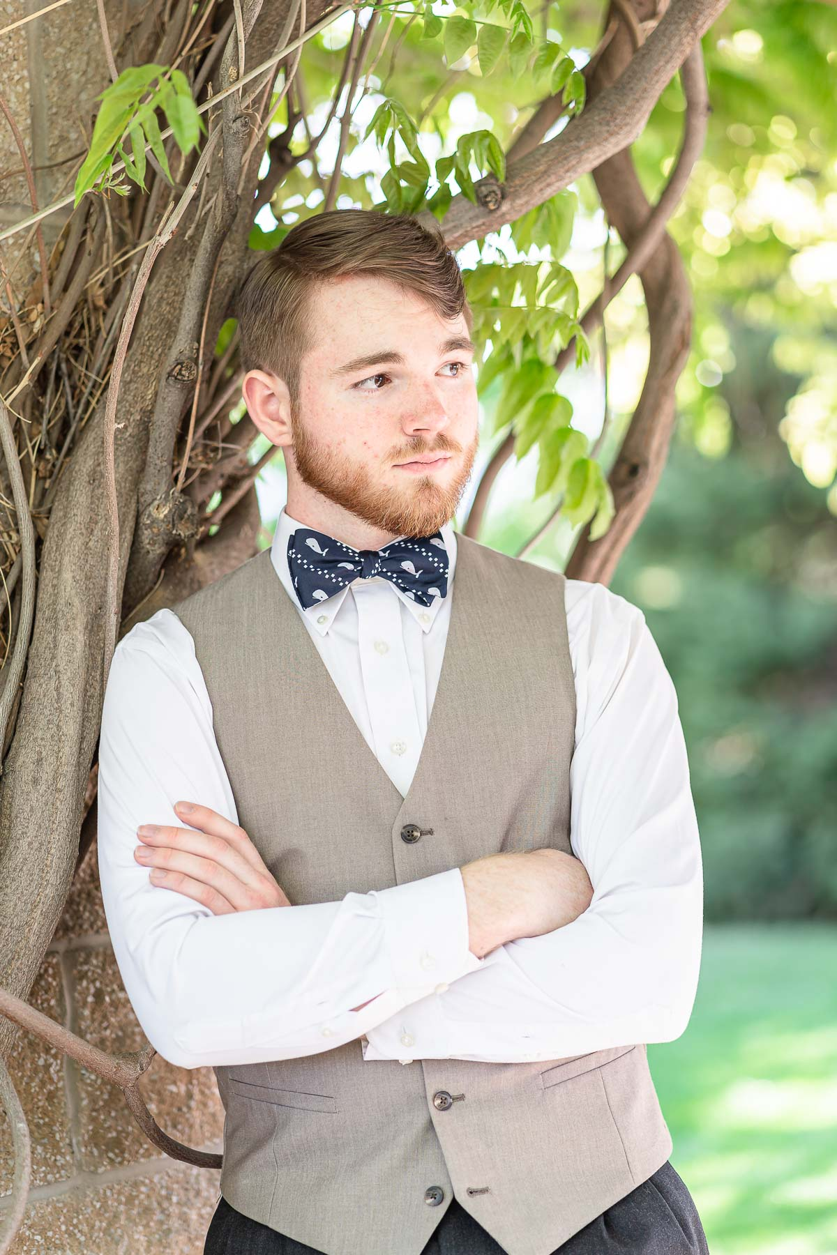 close up of boy in vest and bow tie standing with arms folded in front of vines