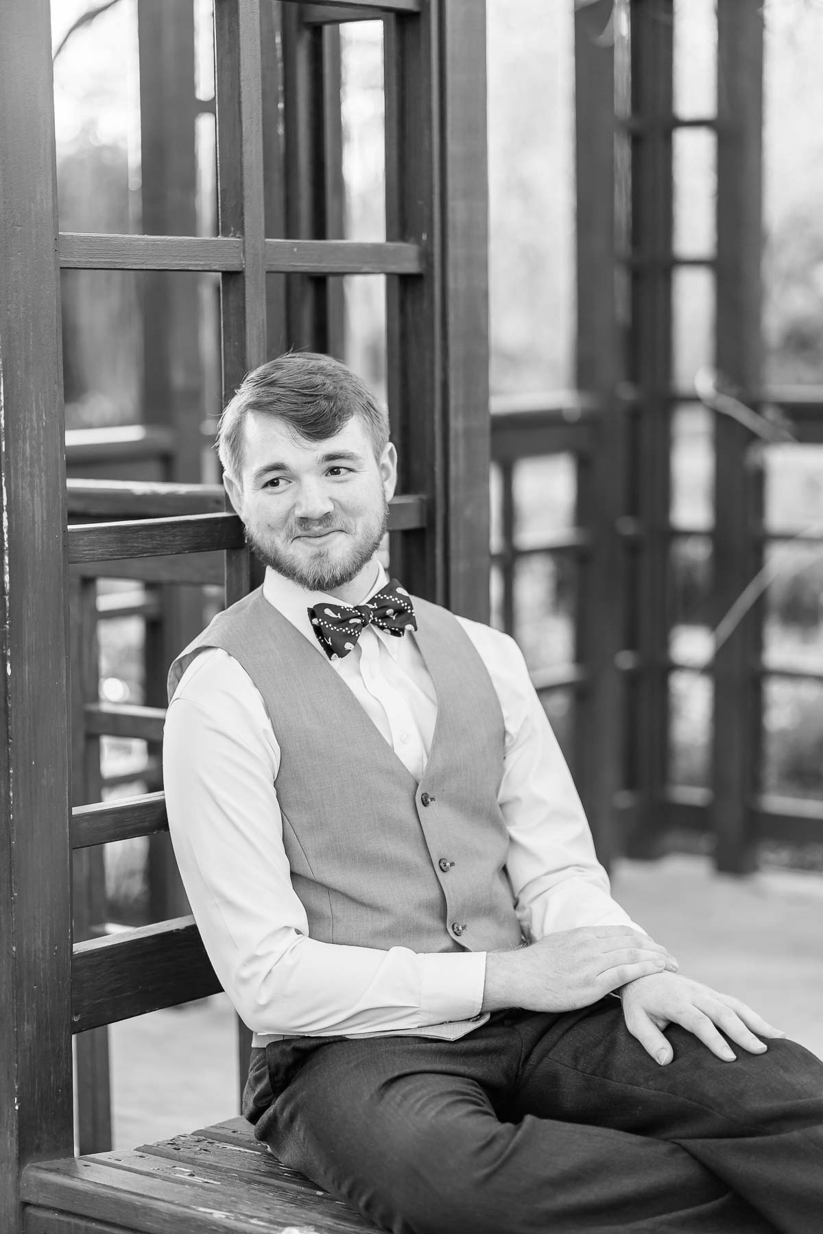 boy in a vest and bow tie sitting and smiling