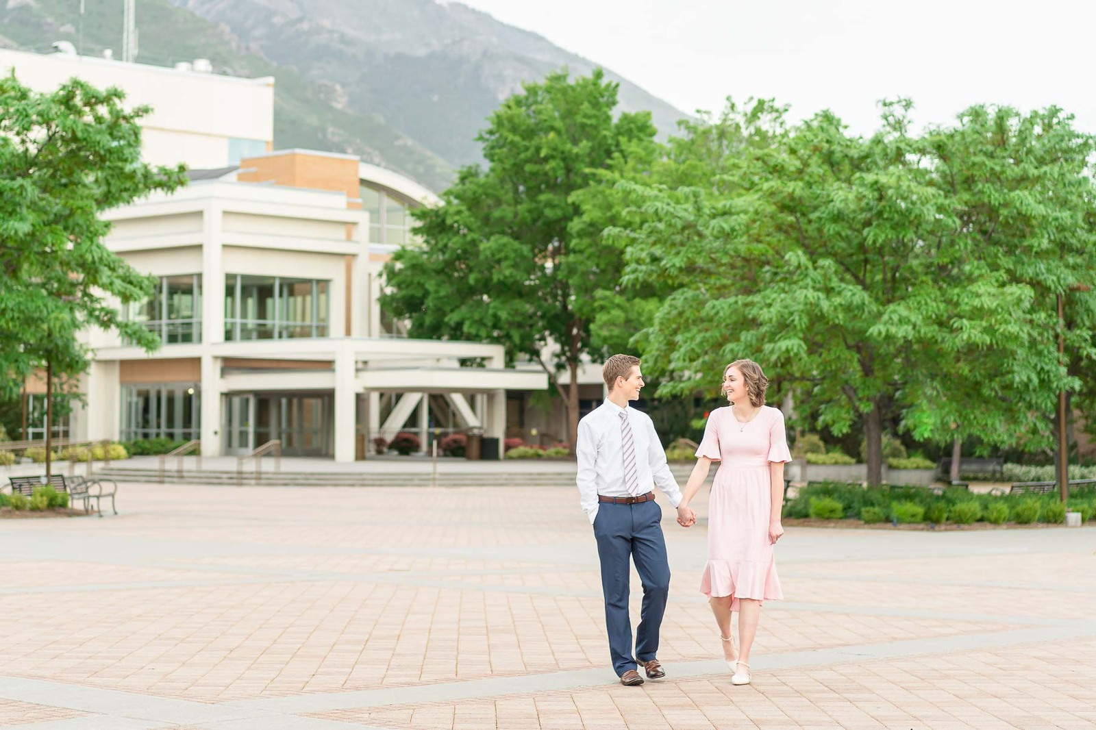 man holding hands with woman in pink walking on BYU campus