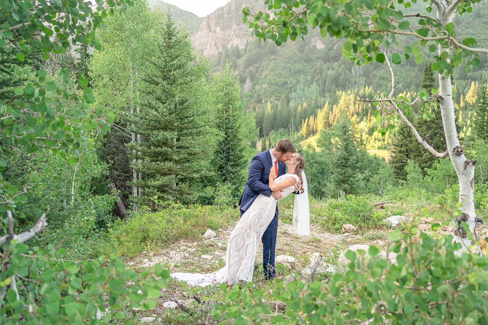groom in blue suit kissing bride in mountains
