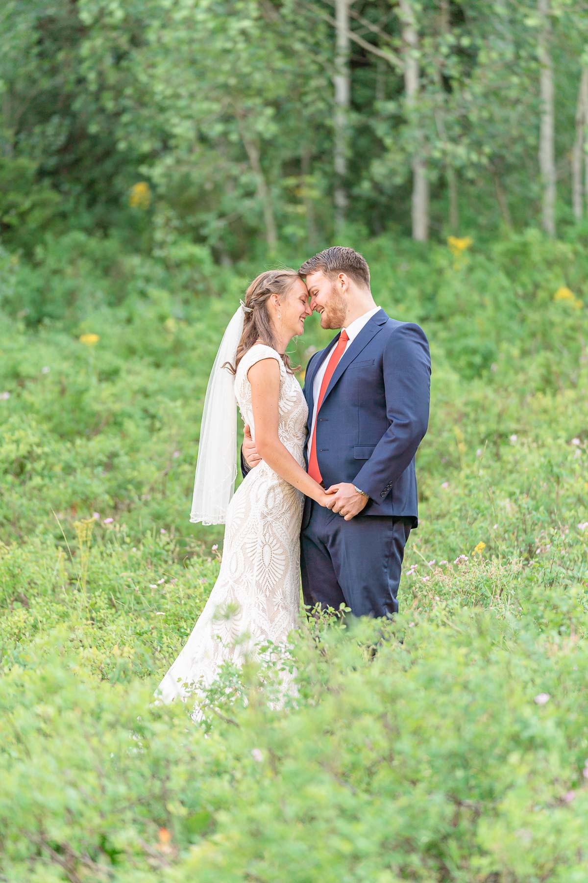bride and groom in blue suit standing in field with yellow wildflowers