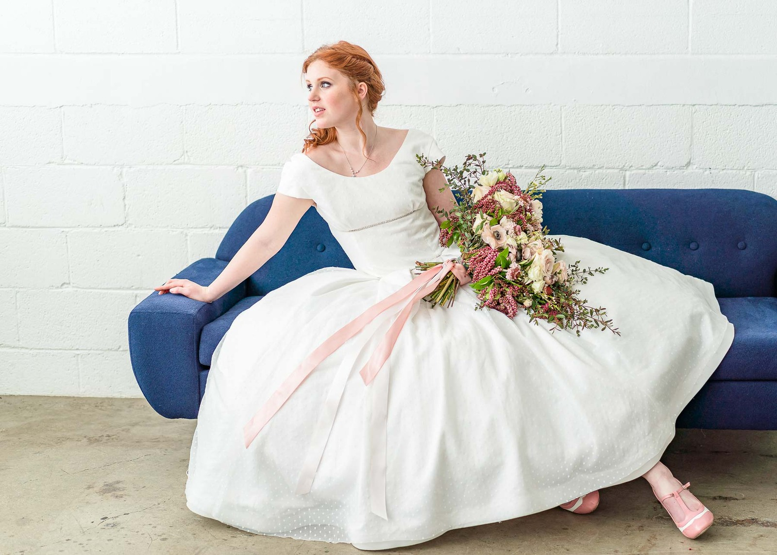 bride with white dress on blue couch with pink shoes