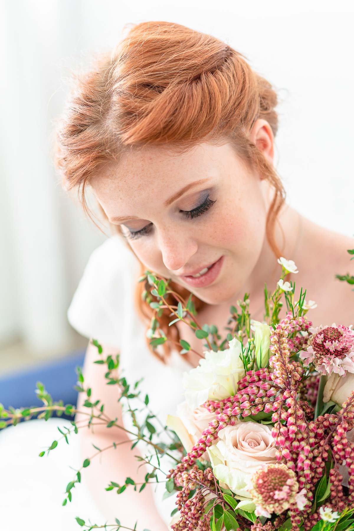 close up of bride looking at bouquet with pink roses and green leaves