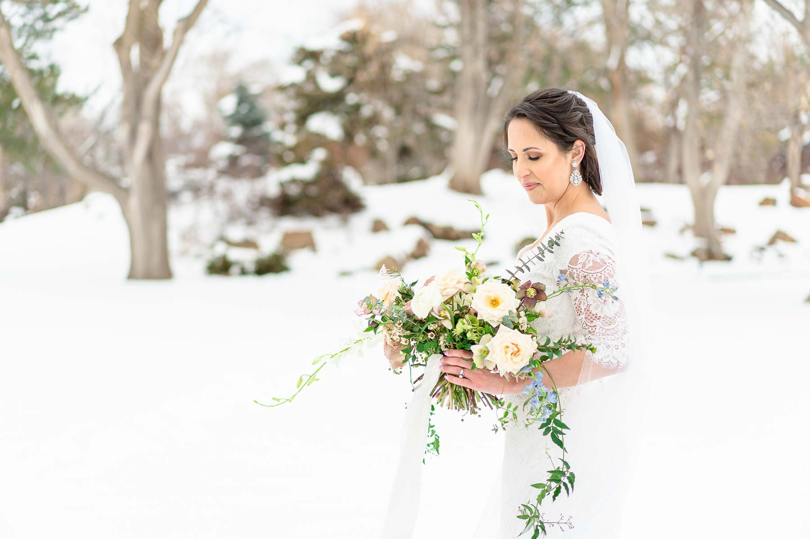 bride looking down at bouquet with white roses and vines in the snow