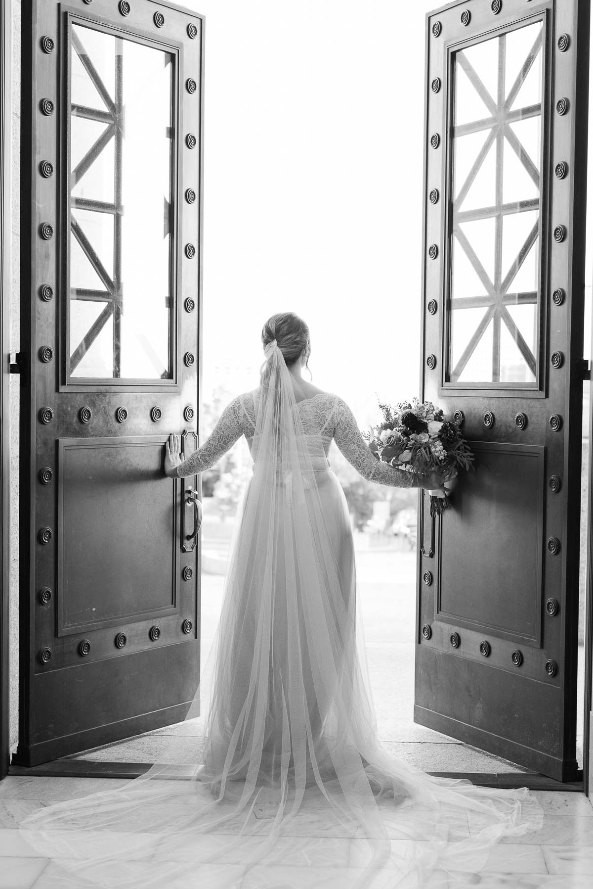bride with long veil and bouquet opening doors
