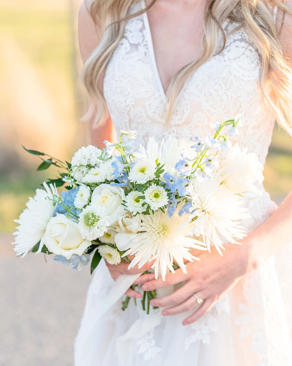 close up of wedding ring and bouquet with white roses, blue flowers, and green leaves
