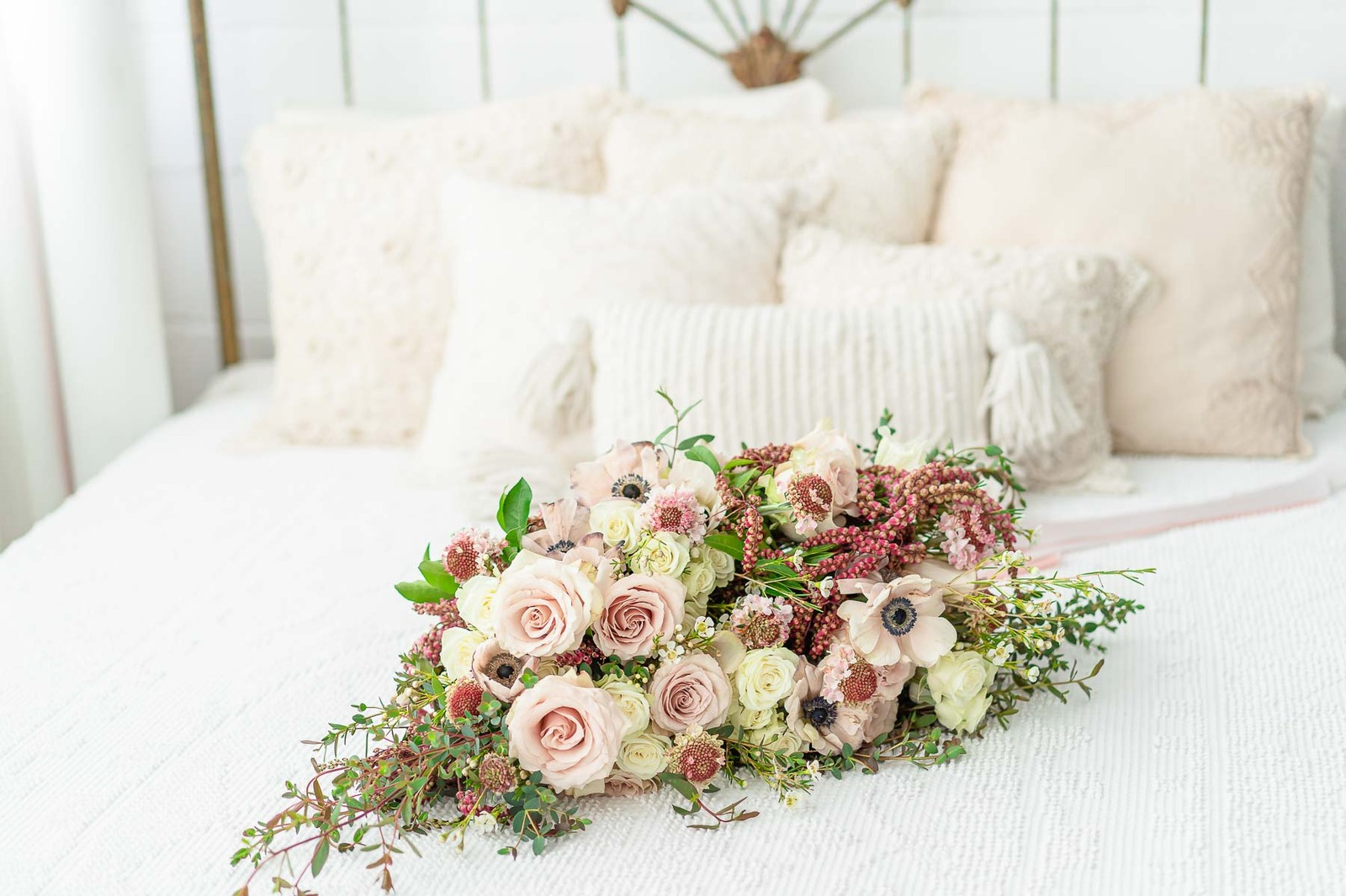 Bouquet with pink roses on bed with off-white pillows