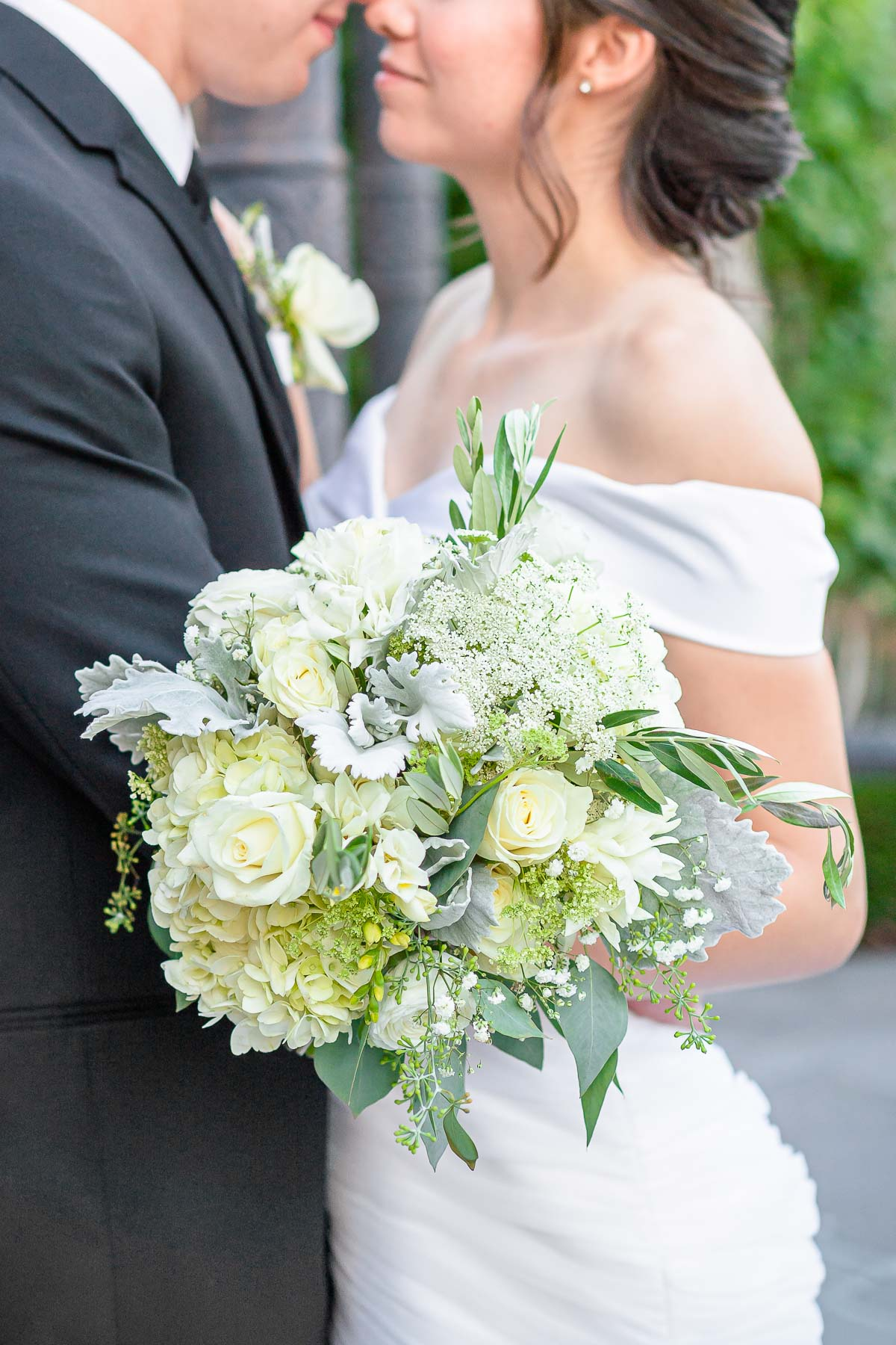 close up of bouquet with white roses and green leaves