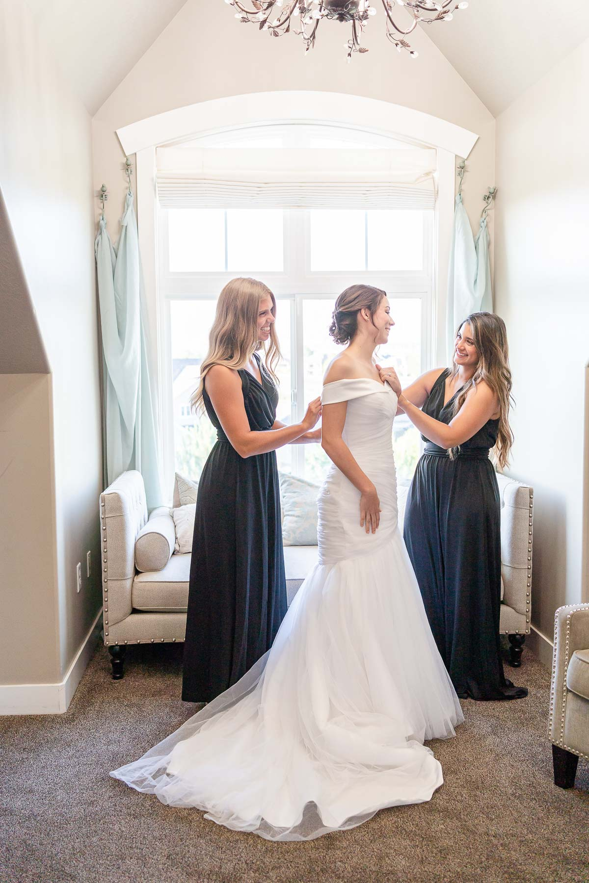 Bride with bridesmaids in black dresses getting ready