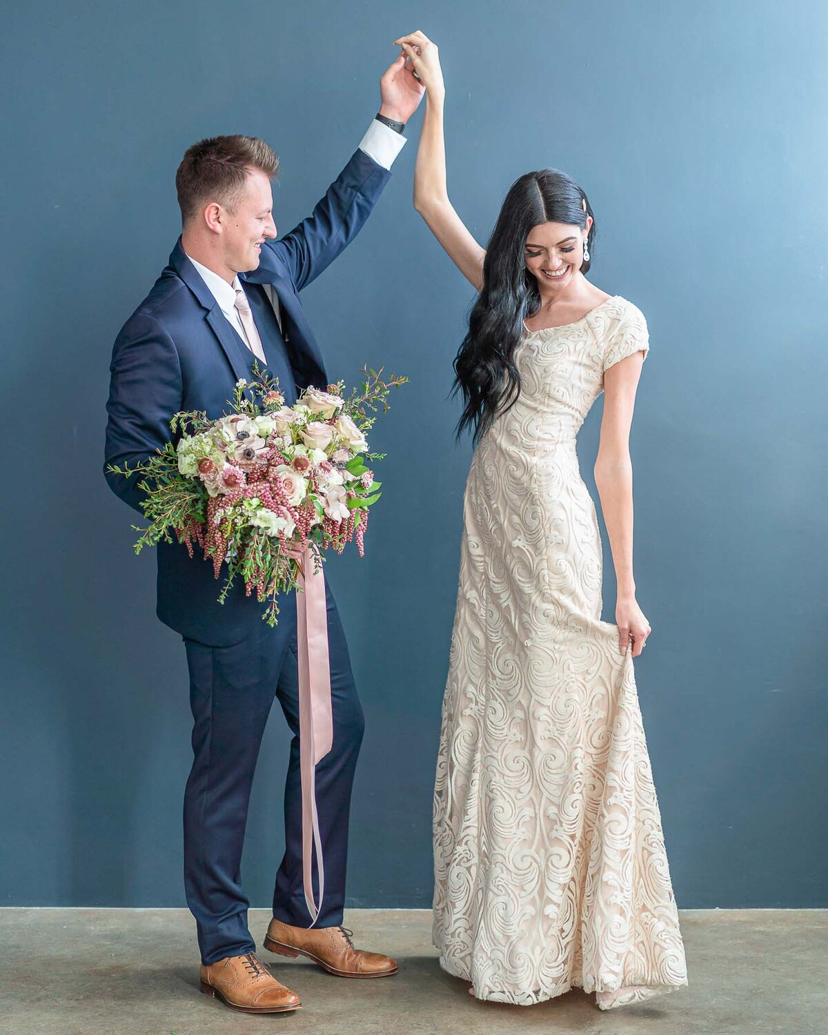 Groom in blue suite with bouquet dancing with bride in cream-colored dress