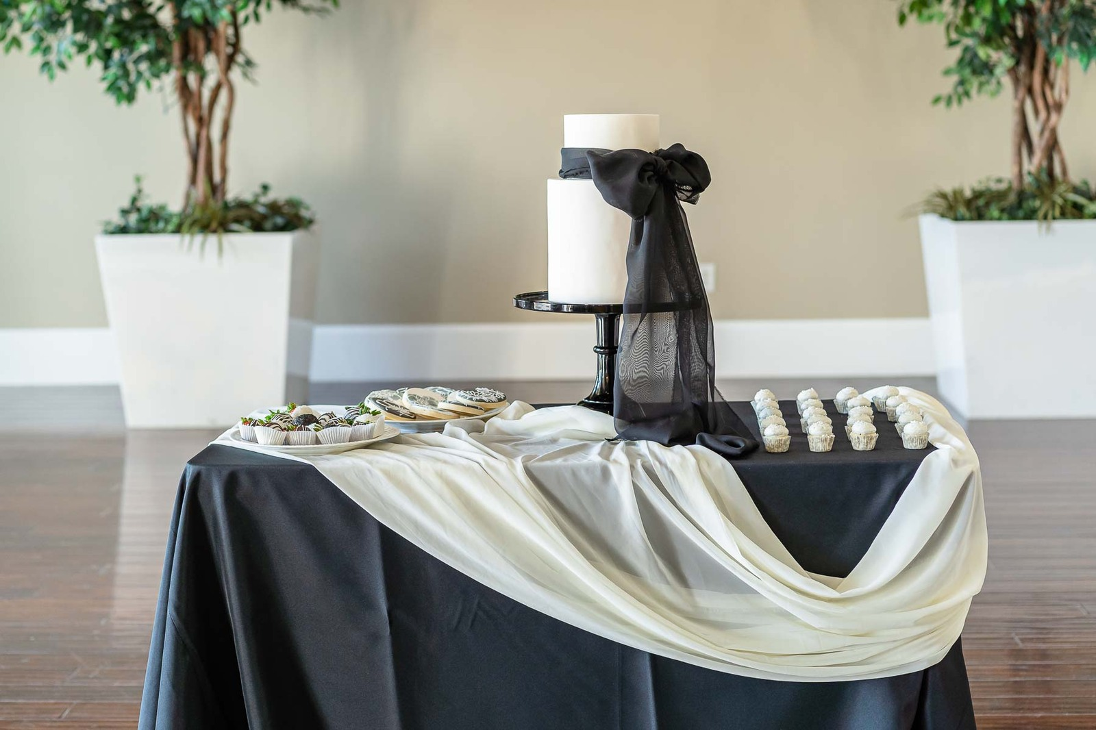 White wedding cake with black bow on table with pastries