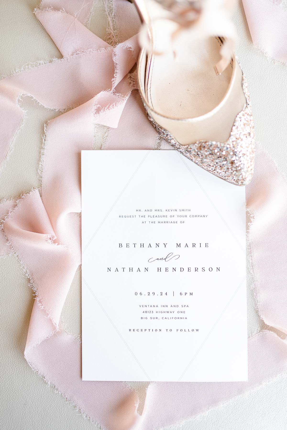 Sparkly Champaign-colored wedding shoes on invitation with pink silk ribbon